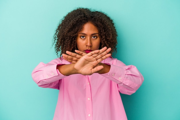否定的なジェスチャーをしている青い背景で隔離の巻き毛を持つ若いアフリカ系アメリカ人女性