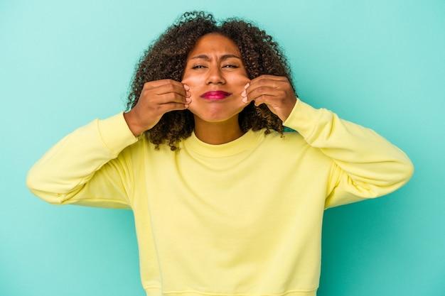 2つのオプションの間で疑う青い背景で隔離の巻き毛を持つ若いアフリカ系アメリカ人女性。