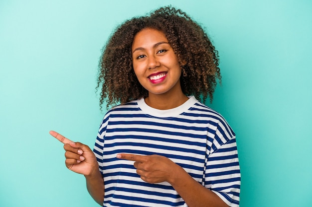 Молодая афро-американская женщина с вьющимися волосами, изолированными на синем фоне, возбуждена, указывая указательными пальцами.