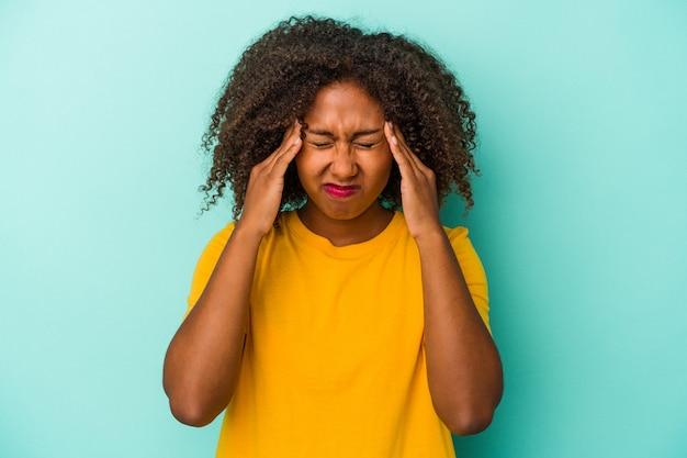 顔の正面に触れて、頭痛を持っている青い背景で隔離の巻き毛を持つ若いアフリカ系アメリカ人の女性。