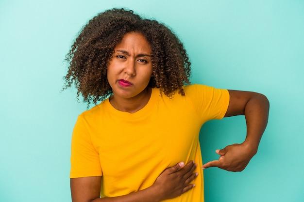 肝臓の痛み、胃の痛みを持っている青い背景に分離された巻き毛の若いアフリカ系アメリカ人女性。