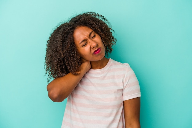 青い背景に孤立した巻き毛の若いアフリカ系アメリカ人女性は、ストレス、マッサージ、手でそれに触れることによる首の痛みを持っています。