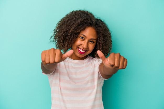 青い背景に孤立した巻き毛の若いアフリカ系アメリカ人女性は、両方の親指を上げて、笑顔で自信を持っています。