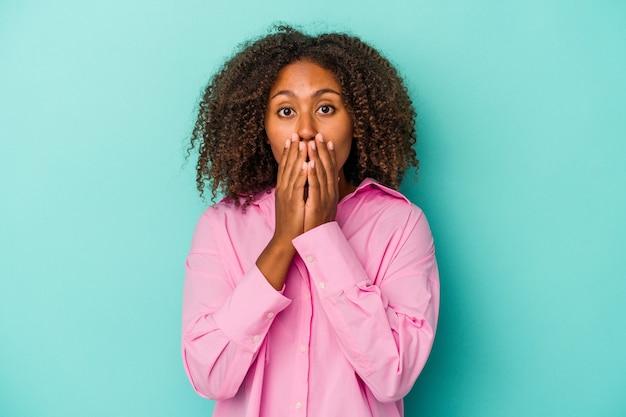青い背景に分離された巻き毛の若いアフリカ系アメリカ人女性は、手で口を覆ってショックを受けました。