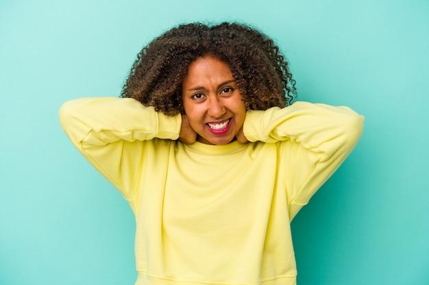頭の後ろに触れて、考えて、選択をする青い背景で隔離の巻き毛を持つ若いアフリカ系アメリカ人の女性。