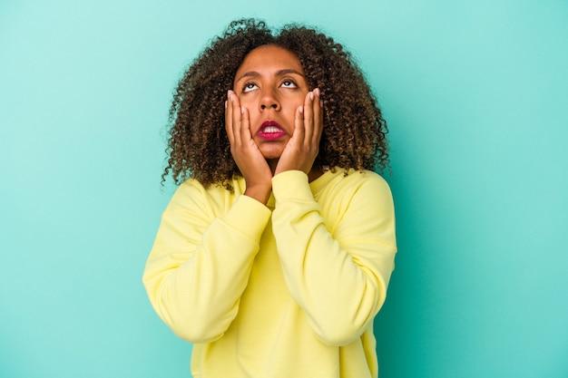 Молодая афро-американская женщина с вьющимися волосами, изолированными на синем фоне, безутешно плачет и плачет.