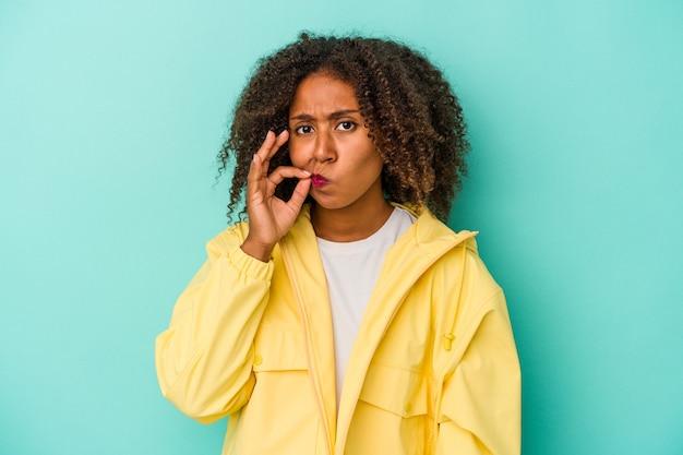 秘密を保持している唇に指で青い背景に分離された巻き毛の若いアフリカ系アメリカ人女性。