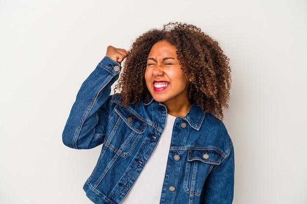 勝利、情熱と熱意、幸せな表現を祝う白い背景で隔離の巻き毛を持つ若いアフリカ系アメリカ人女性。