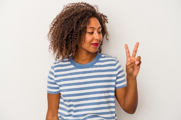 白い背景に分離された巻き毛の若いアフリカ系アメリカ人女性は、指で平和のシンボルを喜んで気楽に示しています。