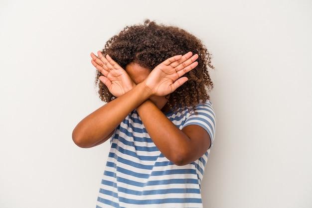 巻き毛の若いアフリカ系アメリカ人女性は、2つの腕を交差させたまま、白い背景で隔離、概念を否定します。