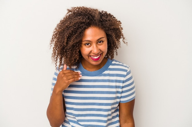 何かについて笑って、手で口を覆って、白い背景で隔離の巻き毛を持つ若いアフリカ系アメリカ人の女性。