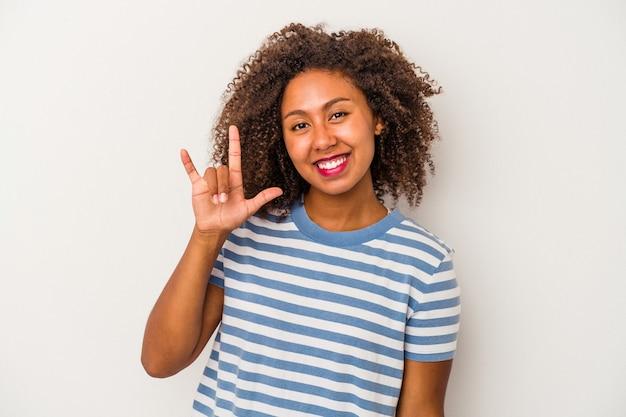 革命の概念として角のジェスチャーを示す白い背景で隔離の巻き毛を持つ若いアフリカ系アメリカ人女性。