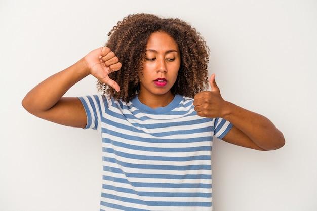 親指を上と親指を下に示す白い背景で隔離の巻き毛を持つ若いアフリカ系アメリカ人女性、難しい選択の概念