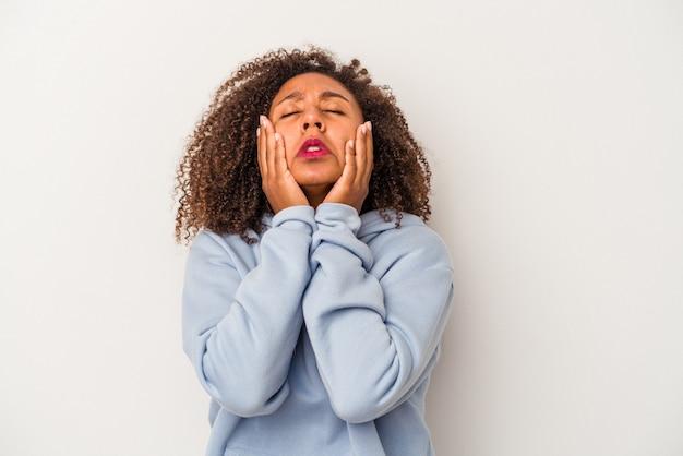 巻き毛の若いアフリカ系アメリカ人女性は、白い背景に孤立して泣き叫びます。