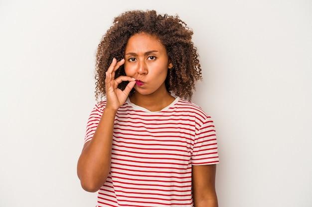 秘密を保持している唇に指で白い背景に分離された巻き毛の若いアフリカ系アメリカ人女性。