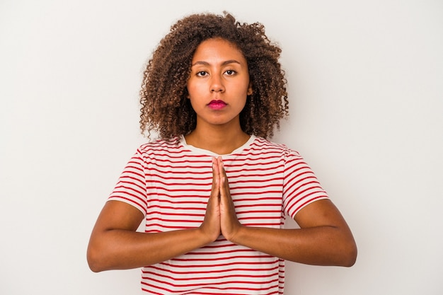 Young african american woman with curly hair isolated on white background praying, showing devotion, religious person looking for divine inspiration.
