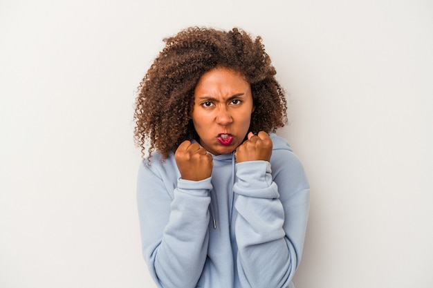 Young african american woman with curly hair isolated on white background showing fist to camera, aggressive facial expression.