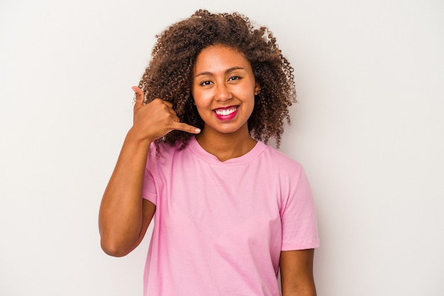 Young african american woman with curly hair isolated on white background showing a mobile phone call gesture with fingers.