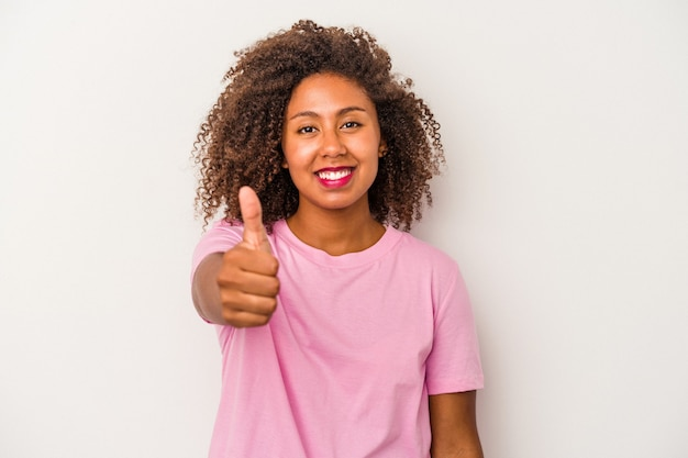 Young african american woman with curly hair isolated on white background smiling and raising thumb up