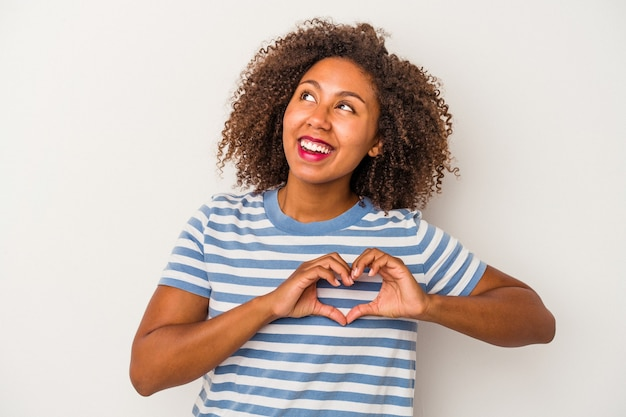Young african american woman with curly hair isolated on white background smiling and showing a heart shape with hands.