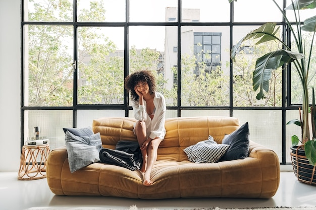 Young african american woman with curly hair sitting on yellow couch looking at camera copy space