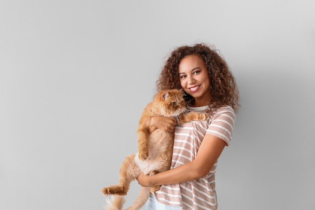 Young african-american woman with cute cat on light