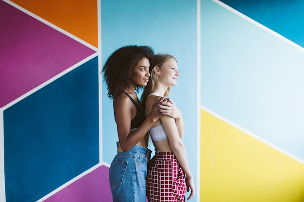 Young african american woman with dark curly hair hugging pretty woman with blond hair dreamily looking aside together with colorful wall  isolated