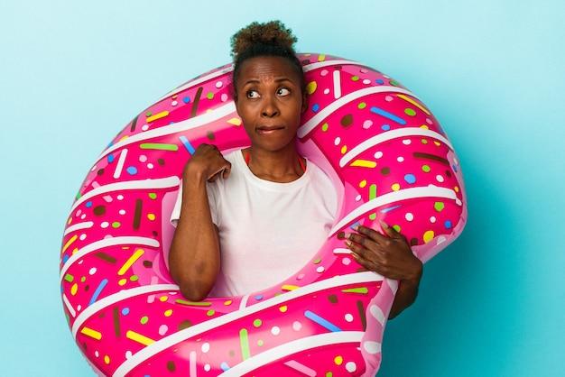 青い背景に分離された膨脹可能なドーナツを持つ若いアフリカ系アメリカ人の女性は混乱し、疑わしく、不安を感じています。
