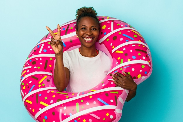 指で2番目を示す青い背景で隔離の膨脹可能なドーナツを持つ若いアフリカ系アメリカ人の女性。