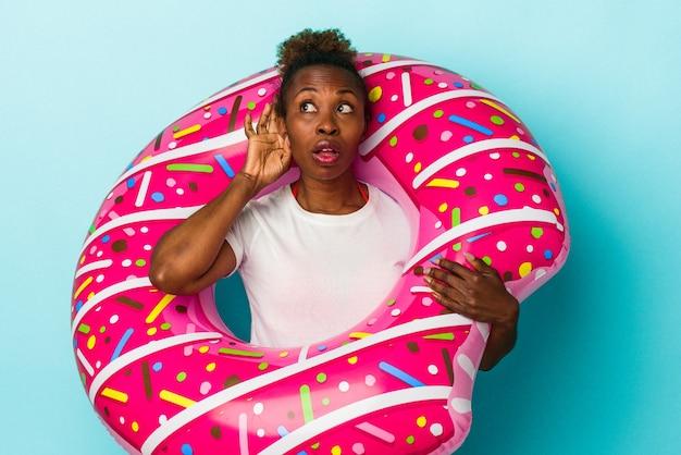 ゴシップを聴こうとしている青い背景に分離された膨脹可能なドーナツを持つ若いアフリカ系アメリカ人の女性。