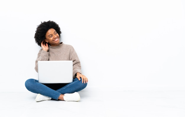 Young african american woman with a laptop sitting on the floor thinking an idea