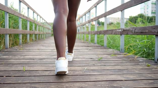 白い快適なスニーカーで長く細い脚を持つ若いアフリカ系アメリカ人の女性は、緑の葦の裏側のビューの間で木製の橋に沿って歩きます