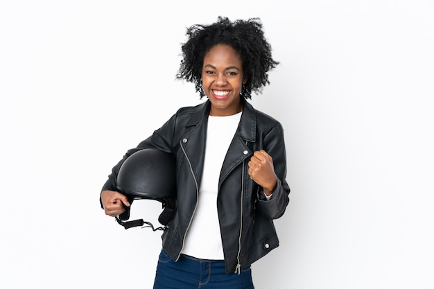 Young african american woman with a motorcycle helmet isolated on white wall celebrating a victory