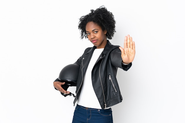 Young african american woman with a motorcycle helmet on white wall making stop gesture with her hand