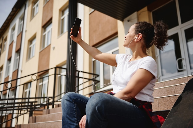 Young african american woman with ponytail and headphones in casual clothing making selfie while sitting on steps