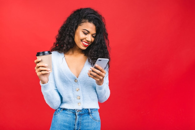 Молодая афро-американская женщина с красными губами пьет кофе