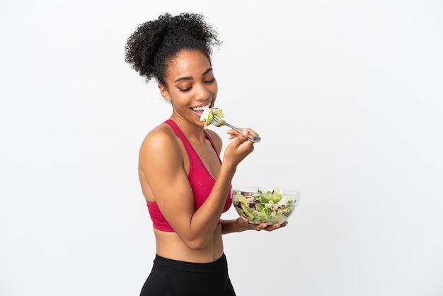 Молодая афро-американская женщина с салатом, изолированные на белом фоне, держит миску салата и смотрит на нее со счастливым выражением лица