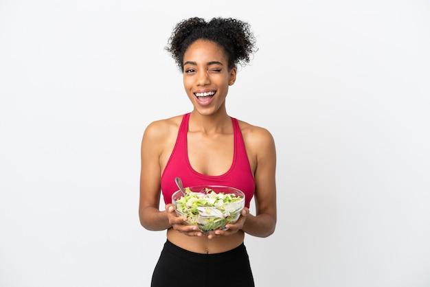 Молодая афро-американская женщина с салатом на белом фоне, подмигивая, держа миску салата