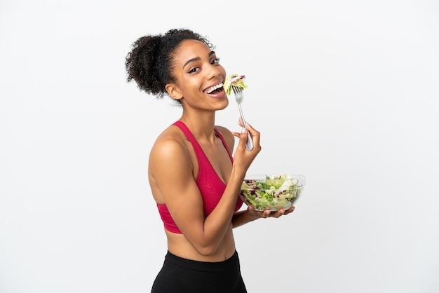 Молодая афро-американская женщина с салатом, изолированным на белом фоне, держит миску салата с счастливым выражением лица