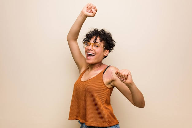 Young african american woman with skin birth mark celebrating a special day, jumps and raise arms with energy.