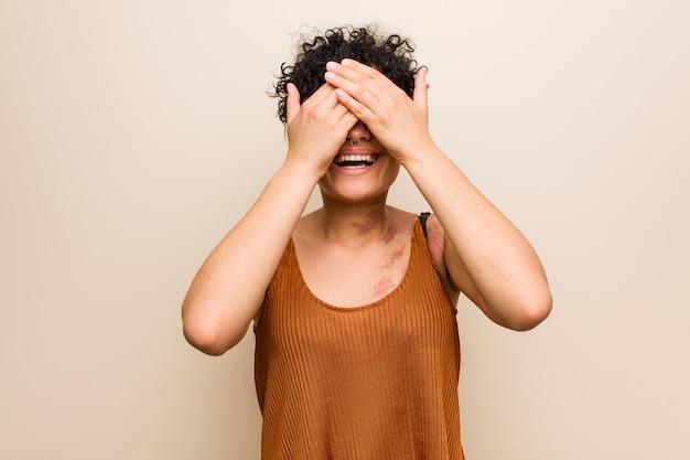 Молодая женщина афроамериканцев с кожей рождения знак покрывает глаза руками, широко улыбается, ожидая сюрприз.