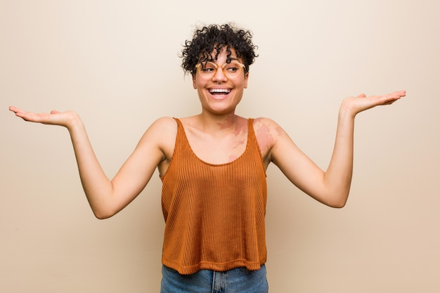 Young african american woman with skin birth mark makes scale with arms, feels happy and confident.