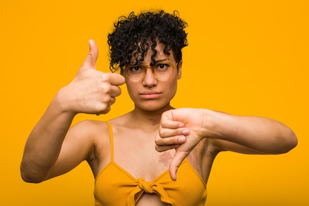Молодая афро-американская женщина с родинкой на коже показывает палец вверх и вниз, трудно выбрать концепцию