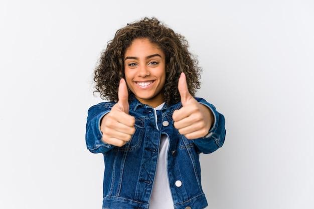 親指を立てて、何かについて歓声を上げ、コンセプトをサポートし、尊重する若いアフリカ系アメリカ人女性。