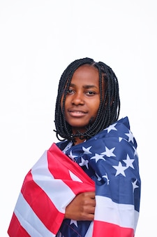 Young african american woman wrapped in usa flag looking at camera with a white background.