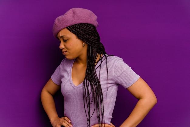 若いアフリカ系アメリカ人の女性背中の痛みに苦しんでいる若いアフリカ系アメリカ人の女性。