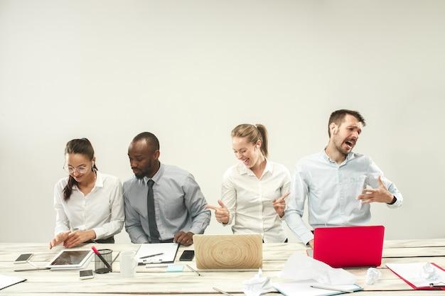 Молодые африканские и кавказские мужчины и женщины сидят в офисе и работают на ноутбуках. бизнес, эмоции, команда, работа в команде, рабочее место, лидерство, концепция встречи. разные эмоции коллег
