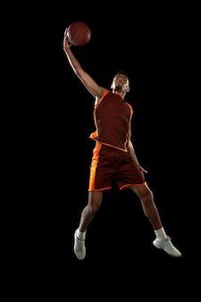검은 스튜디오 배경에서 훈련하는 젊은 아프리카 농구 선수.