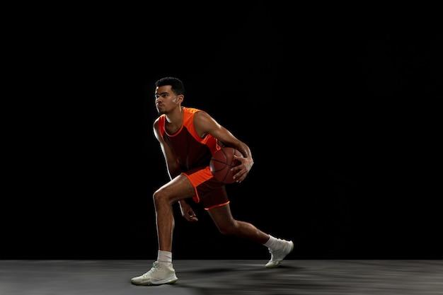 검은 스튜디오 배경에서 훈련하는 젊은 아프리카 농구 선수
