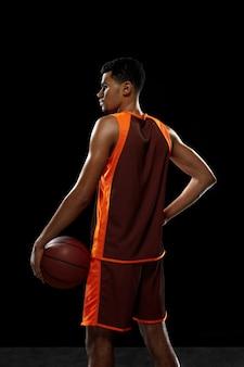 Обучение молодых африканских баскетболистов на фоне черной студии.